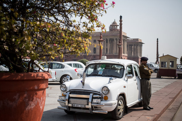 A officer of the Indian CRPF (Central Reserve Police Force) is waiting at his Ambassador car, the beacon covered, which he is driving in service of a government employee working at the offices of Raisina Hill, housing India's most important government buildings, in New Delhi on March 06, 2014. (Photo by Enrico Fabian/The Washington Post)