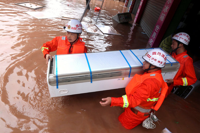 Rescuers move an electrical appliance from a shop at a flooded area in Luzhou, Sichuan Province, China, June 19, 2016. (Photo by Reuters/Stringer)