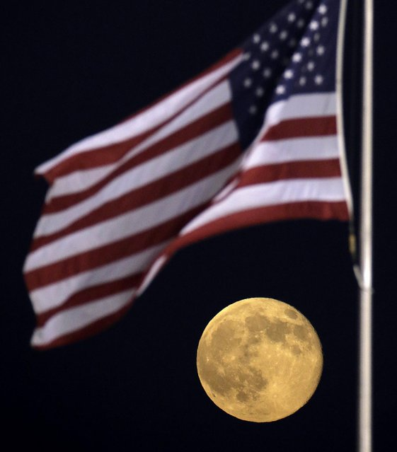 A perigee moon rises beyond an American flag at Kauffman Stadium during a game between the Kansas City Royals and the Detroit Tigers in Kansas City. (Photo by Charlie Riedel/Associated Press)