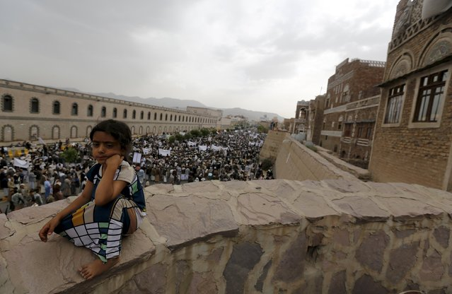 A girl sits on a wall as Houthi followers demonstrate against Saudi-led air strikes in Yemen's capital Sanaa July 24, 2015. (Photo by Khaled Abdullah/Reuters)