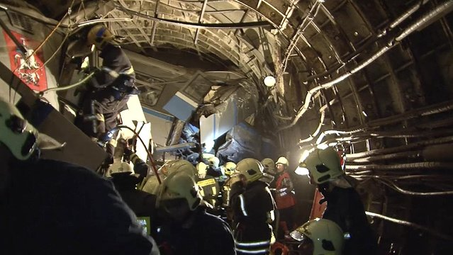In this frame grab provided by the Russian Ministry for Emergency Situations shows frame grab from a video showing rescue teams working inside the tunnel where several cars of the wrecked train look almost coiled, occupying the entire space of the tunnel of Moscow subway in Moscow, Russia, on Tuesday, July 15, 2014. Workers were seen trying to force open the mangled doors of the car where dead bodies are supposed to be. (Photo by AP Photo/Russian Emergency Situation Ministry)