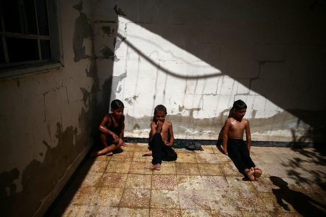 Boys rest after swimming to cool down from heat, in the rebel held besieged town of Douma, eastern Damascus suburb of Ghouta, Syria, June 23, 2016. (Photo by Bassam Khabieh/Reuters)