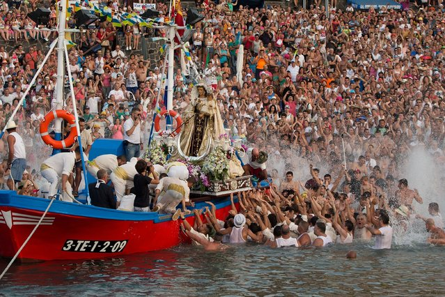 People spread water as carriers of the Great God Power brotherhood load the Virgen del Carmen statue on July 15, 2014 at Puerto de la Cruz dock on the Canary island of Tenerife, Spain. (Photo by Gonzalo Arroyo Moreno/Getty Images)