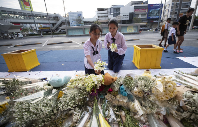 Students offer flowers at the scene of a deadly mass shooting outside the Terminal 21 shopping mall in Korat, Nakhon Ratchasima, Thailand Tuesday, February 11, 2020. A soldier carried out the country's worst mass shooting in an hourslong siege at the shopping mall. (Photo by Sakchai Lalit/AP Photo)