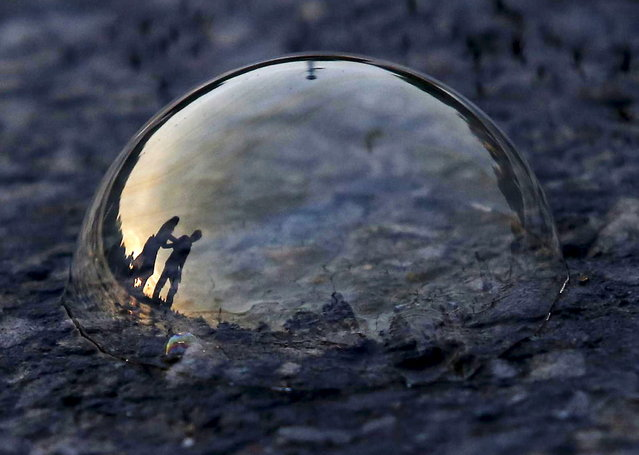 People are reflected on a soap bubble lying on a road during the evening in New Delhi, India, June 23, 2015. (Photo by Anindito Mukherjee/Reuters)