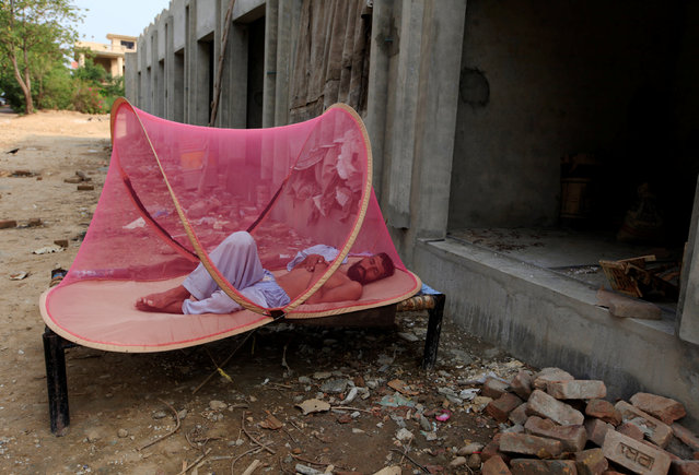 A labourer sleeps under a mosquito net in front of under construction shops on a hot day in Islamabad, Pakistan, June 21, 2016. (Photo by Faisal Mahmood/Reuters)