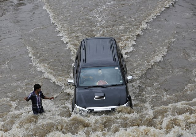 A car drives past a man through a flooded road after heavy monsoon rains in the western Indian city of Ahmedabad July 30, 2014. July, the second month of the monsoon season, usually gets the maximum rainfall, accounting for about a third of the seasonal downpour. (Photo by Amit Dave/Reuters)