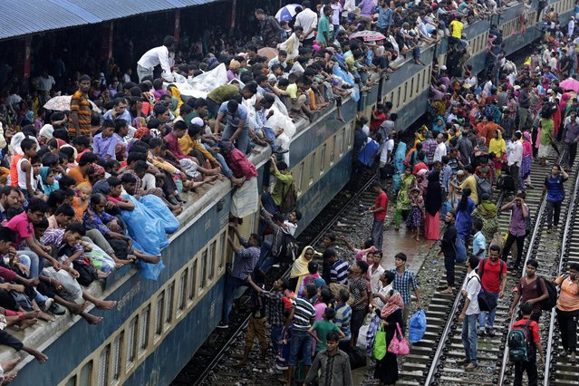 People wait to board trains as they travel to their villages ahead of the Eid Al-Fitr celebrations at the Airport Railway Station in Dhaka, Bangladesh, 05 July 2016. Bangladeshi Muslims living in Dhaka, the capital city, will travel to villages to celebrate Eid Al-Fitr, which marks the end of the Muslim holy month of Ramadan. (Photo by Abir Abdullah/EPA)