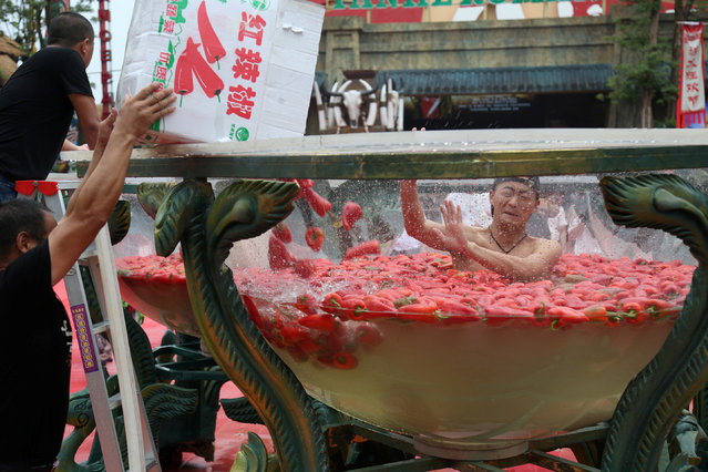 A man sits in a water vat filled with red chilies as he takes part in a chili-eating competition at a scenic area in Ningxiang, Hunan province, China, August 12, 2017. (Photo by Reuters/China Stringer Network)