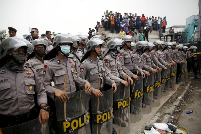 Indonesian policemen stand guard on a street after clashing with residents at Kampung Pulo district in Jakarta, August 20, 2015. (Photo by Darren Whiteside/Reuters)