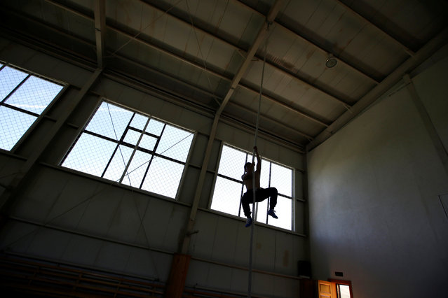 A training partner of Mongolia's Olympic wrestler team climbs a rope during a daily training session at the Mongolia Women's National Wrestling Team training centre in Bayanzurkh district of Ulaanbaatar, Mongolia, July 1, 2016. (Photo by Jason Lee/Reuters)