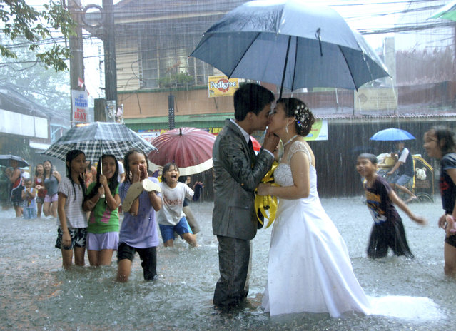 Ramoncito Campo kisses his wife Hernelie Ruazol Campo on a flooded street during a southwest monsoon that battered Manila August 8, 2012. The newly-wed couple pushed through with their scheduled wedding despite severe flooding that inundated wide areas of the capital and nearby nine provinces. (Photo by Reuters/Courtesy of Ramoncito Campo)