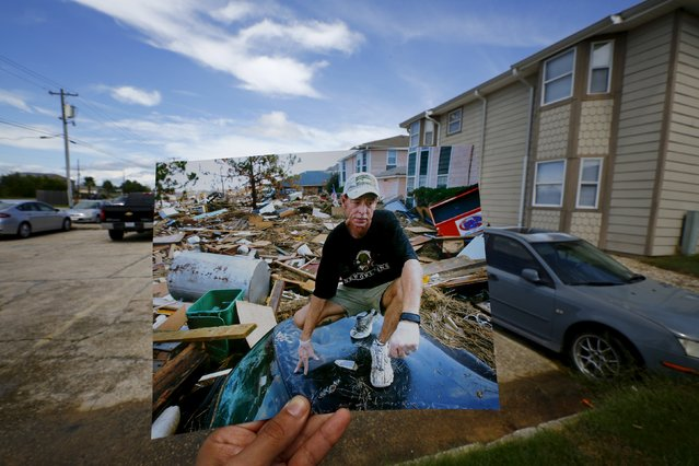 Photographer Carlos Barria holds a print of a photograph he took in 2005, as he matches it up at the same location 10 years on, in North Shore, northwest of New Orleans, United States, August 17, 2015. The print shows Michael Rehage squatting on the roof of his car, September 12, 2005, after Hurricane Katrina struck. (Photo by Carlos Barria/Reuters)