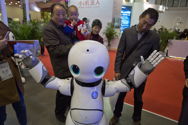 Visitors look at the Canbot companion robot during the World Robot Conference in Beijing, China, Friday, October 21, 2016. (Photo by Ng Han Guan/AP Photo)
