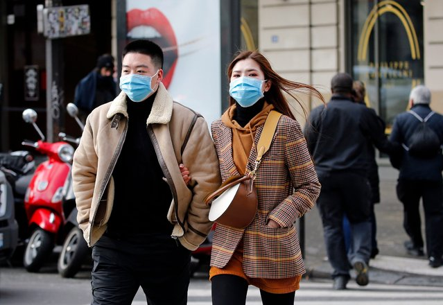 Tourists wearing protective masks walk the streets of Paris on March 3, 2020 in Paris, France. Due to a sharp increase in the number of cases of coronavirus (COVID-19) declared in Paris and throughout France, several sporting, cultural and festive events have been postponed or canceled. The epidemic has exceeded 3,000 dead for more than 86,000 infections in sixty countries. In France, 130 cases are now confirmed, in twelve regions in total. (Photo by Chesnot/Getty Images)
