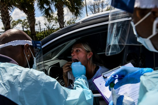 """A medical personnel member takes samples of Lee Dinzik (29) at a """"drive-thru"""" coronavirus testing lab set up by a local community center in West Palm Beach 75 miles north of Miami, on March 16, 2020. Stocks tumbled on March 16, 2020 despite emergency central bank measures to prop up the virus-battered global economy, as countries across Europe started the week in lockdown and major US cities shut bars and restaurants. The virus has upended society around the planet, with governments imposing restrictions rarely seen outside wartime, including the closing of borders, home quarantine orders and the scrapping of public events including major sporting fixtures. (Photo by Chandan Khanna/AFP Photo)"""