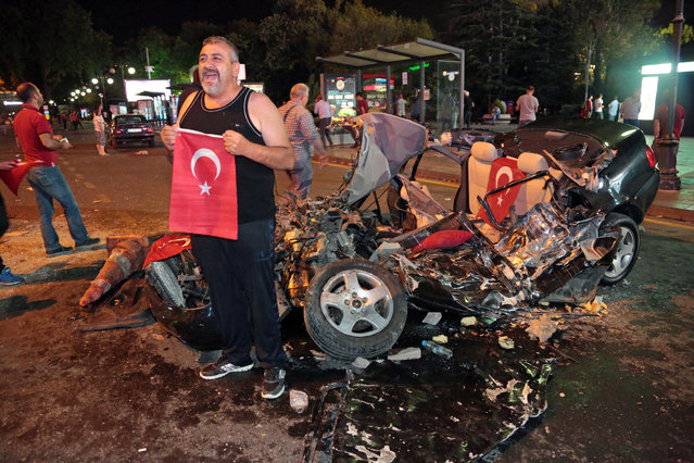 A man poses with the flag of Turkey in front of a damaged car, crashed by a military tank as people gather in Kizilay Square to protest against a military coup in Ankara, Turkey, early Saturday, July 16, 2016. (Photo by Burhan Ozbilici/AP Photo)