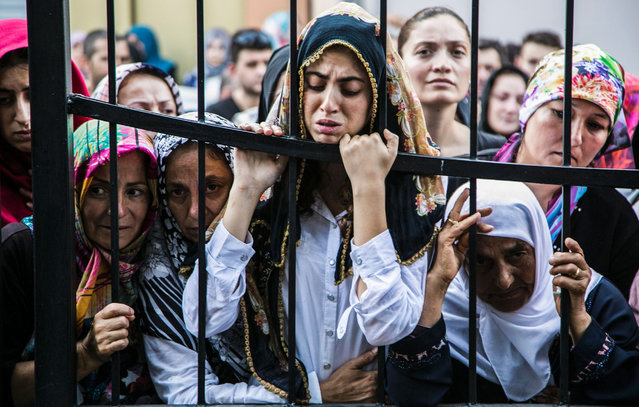 """Women react during the funeral of a victim of the failed July 15 coup attempt in Istanbul on July 17, 2016. Turkish President Recep Tayyip Erdogan vowed Sunday to purge the """"virus"""" within state bodies, during a speech at the funeral of victims killed during the coup bid he blames on his enemy Fethullah Gulen. (Photo by Gurcan Ozturk/AFP Photo)"""