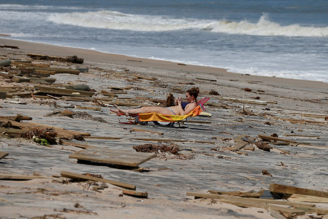 A woman suntans amongst debris on the beach after Hurricane Irma passed the area in Ponte Vedra Beach, Florida, U.S., September 12, 2017. (Photo by Chris Wattie/Reuters)