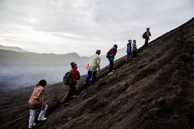 """Indonesian Tenggerese Hindu worshippers climb across Mount Bromo's """"Sea of Sand"""" during the Yadnya Kasada Festival at the crater of Mount Bromo in Probolinggo, East Java, Indonesia, 21 July 2016. (Photo by Fully Handoko/EPA)"""