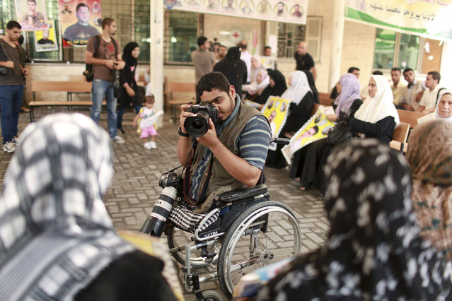 Wheelchair-bound Palestinian freelance photographer Moamen Qreiqea takes pictures of protesters calling for the release of Palestinian prisoners from Israeli jails, in Gaza City October 1, 2012. Qreiqea, 25, lost both his legs in an Israeli air strike in 2008 while taking pictures east of Gaza. The father of two is determined to continue his career despite his disability. (Photo by Suhaib Salem/Reuters)