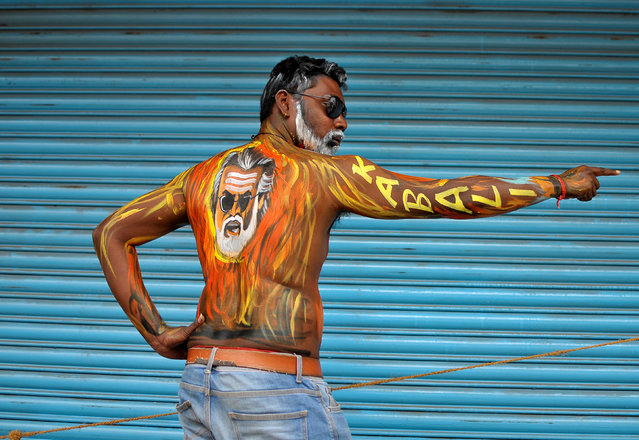 "A fan with his body painted with an image of actor Rajinikanth poses outside a movie theatre showcasing the Tamil film ""Kabali"" in Bengaluru, India, July 22, 2016. (Photo by Abhishek N. Chinnappa/Reuters)"