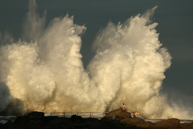 A man watches a wave hit a rock pool at Curl Curl beach as large swell hits the East Coast of Australia on June 6, 2016 in Sydney, Australia. Torrential rain over the weekend saw streets and homes flooded while wind gusts up to 120km per hour brought down trees and powerlines. A king tide has also seen beachside homes evacuated on Sydney's northern beaches as large waves erode the coast. (Photo by Cameron Spencer/Getty Images)