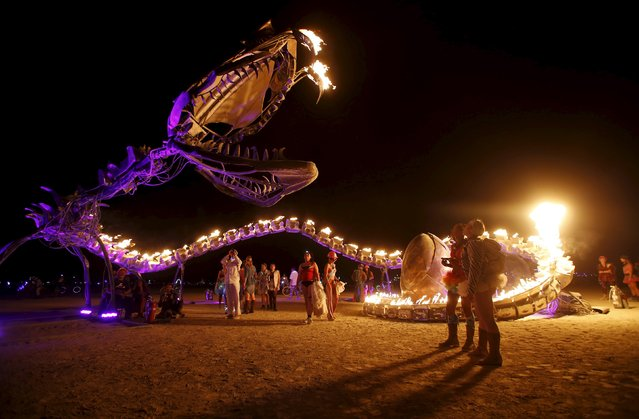 "People gather at the art installation Serpent Mother during the Burning Man 2015 ""Carnival of Mirrors"" arts and music festival in the Black Rock Desert of Nevada, September 1, 2015. Participants are still arriving from all over the world for the sold-out festival to spend a week in the remote desert to experience art, music and the unique community that develops. (Photo by Jim Urquhart/Reuters)"