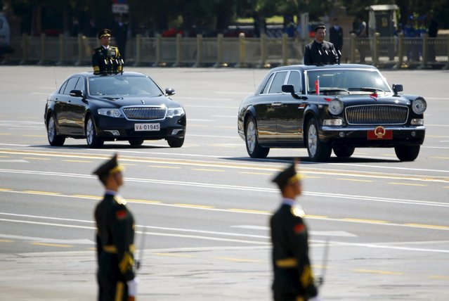 Chinese President Xi Jinping stands in a car (R) after he reviewed the army, during the military parade marking the 70th anniversary of the end of World War Two, in Beijing, China, September 3, 2015. (Photo by Damir Sagolj/Reuters)