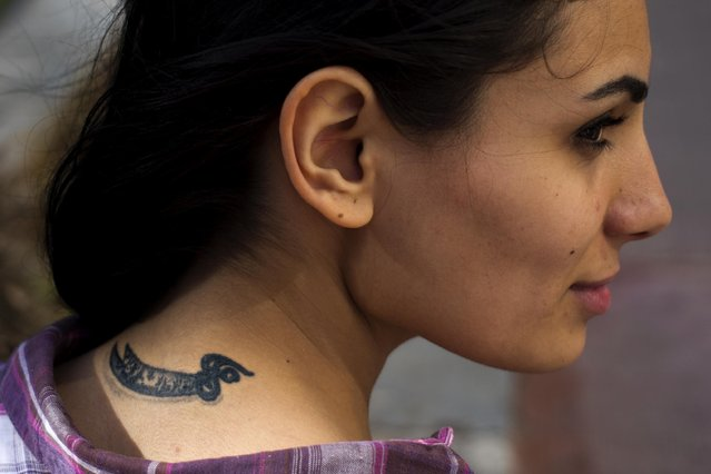 In this Wednesday, May 25, 2016 photo, Farah Najm, 21, an aviation maintenance student, poses for a photo showing her tattoo of the sword of Shiite Muslims' first Imam Ali, in Beirut, Lebanon. (Photo by Hassan Ammar/AP Photo)