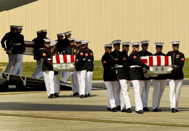 Transfer cases are carried into a hangar during the Transfer of Remains Ceremony marking the return to the United States of the remains of the four Americans killed this week in Benghazi, Libya, at Joint Base Andrews. (Photo by Molly Riley/Polaris via Abaca Press/MCT)