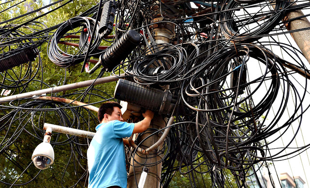 A worker makes repairs below electricity and communications cables on a pylon in Beijing on September 5, 2014. Shanghai stocks closed at a 17-month high on September 5 on hopes the Chinese government will introduce fresh measures to kickstart the world's number two economy. (Photo by Greg Baker/AFP Photo)
