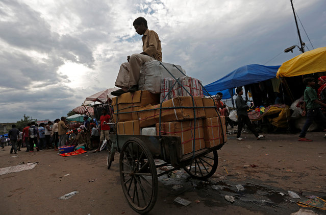 A labourer sits on top of a rickshaw loaded with boxes at a wholesale market in the old quarter of Delhi, India, August 2, 2016. (Photo by Adnan Abidi/Reuters)