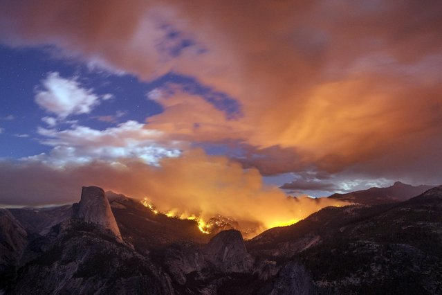 A wildfire burns next to Half Dome in Yosemite National Park, Calif, Sunday, September 7, 2014. As of Monday, the fire has burned through about four square miles. (Photo by AP Photo/Michaelfrye.com)