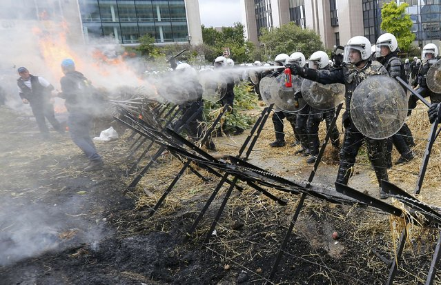 Belgian riot police officers clash with protesters as farmers and dairy farmers from all over Europe take part in a demonstration outside an European Union farm ministers emergency meeting at the EU Council headquarters in Brussels, Belgium, September 7, 2015. (Photo by Yves Herman/Reuters)