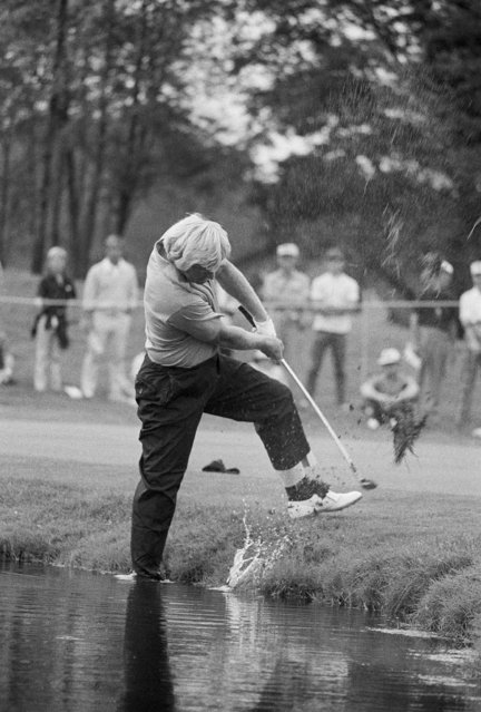 Jack Nicklaus hits the ball to the 16th green at the Firestone Country Club in Akron, Ohio during first round of the World Series of Golf, September 8, 1973. His third shot on the 625 yard hole stuck in the lake's bank and forced Nicklaus to wade into the water. He first took off his shoe and tested the water then decided he could get a better stance with his shoe on and made the shot. (Photo by Steve Pyle/AP Photo)