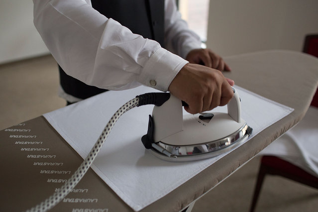 A student irons napkins before buttling at a formal dinner at The International Butler Academy China on September 16, 2014 in Chengdu, China. (Photo by Taylor Weidman/Getty Images)