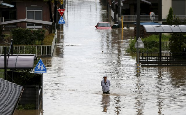 A man wades through a residential area flooded by the Kinugawa river, caused by typhoon Etau, in Joso, Ibaraki prefecture, Japan, September 10, 2015. (Photo by Issei Kato/Reuters)