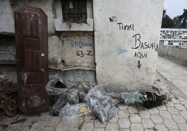 "The mummified body of a woman lies on the floor and next to a wall with the writing ""No littering here"" during exhumation works at the Verbena cemetery in Guatemala City April 17, 2013. (Photo by Jorge Dan Lopez/Reuters)"