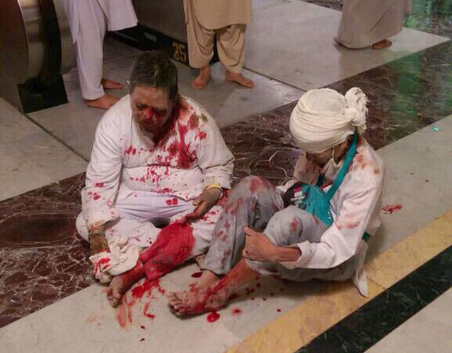 Wounded pilgrims sit on the floor after a crane collapse that killed dozens inside the Grand Mosque in Mecca, Saudi Arabia, Friday, September 11, 2015. The accident happened as pilgrims from around the world converged on the city, Islam's holiest site, for the annual Hajj pilgrimage, which takes place this month. (Photo by AP Photo)