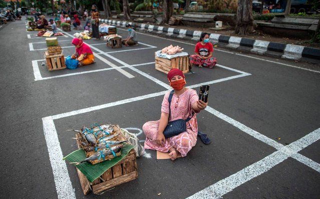 Vendors sit in allocated lots to observe social distancing amid fears over the spread of the COVID-19 coronavirus outbreak along a street in Surabaya, Indonesia in June 2, 2020. (Photo by Juni Kriswanto/AFP Photo)