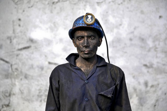 In this Wednesday, May 7, 2014 photo, an Iranian coal miner with his face smeared black from coal poses for a photograph at a mine near the city of Zirab 212 kilometers (132 miles) northeast of the capital Tehran, on a mountain in Mazandaran province, Iran. The workers who put in long hours in often dangerous conditions and make just $300 a month, little more than minimum wage. (Photo by Ebrahim Noroozi/AP Photo)
