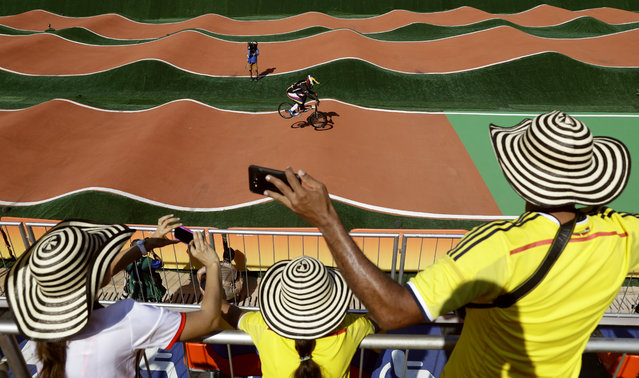 Colombian fans watch as Mariana Pajon of Colombia, background, competes in the women's seeding run at the Olympic BMX Center during the 2016 Summer Olympics in Rio de Janeiro, Brazil, Wednesday, August 17, 2016. (Photo by Pavel Golovkin/AP Photo)