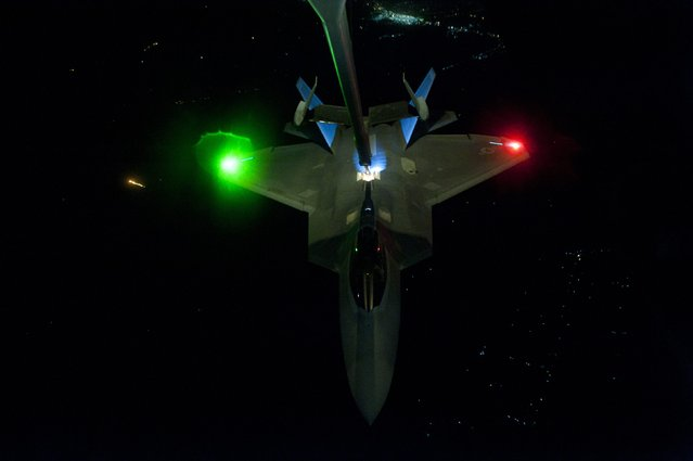 A U.S Air Force KC-10 Extender refuels an F-22 Raptor fighter aircraft prior to strike operations in Syria in this September 26, 2014 photo released on September 29, 2014. These aircraft were part of a strike package that was engaging ISIL targets in Syria. (Photo by Russ Scalf/Reuters/U.S. Air Force)