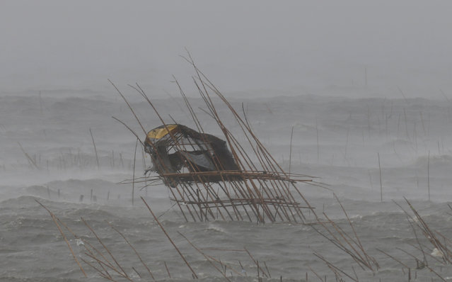 A fisherman's house in the middle of a fish pen leans to one side as it is pounded by waves, strong winds and rain brought by Typhoon Rammasun in the coastal town of Bacoor, Cavite, southwest of Manila, July 16, 2014. (Photo by Erik De Castro/Reuters)