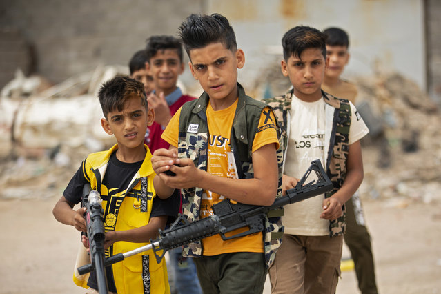 Iraqi children play with plastic toy guns as they celebrate Eid al-Fitr, the Muslim holiday which starts at the conclusion of the holy fasting month of Ramadan, in the southern Iraqi city of Basra on May 25, 2020. Muslims around the world began marking a sombre Eid al-Fitr, many under coronavirus lockdown, but lax restrictions offered respite to worshippers in some countries despite fears of skyrocketing infections. (Photo by Hussein Faleh/AFP Photo)