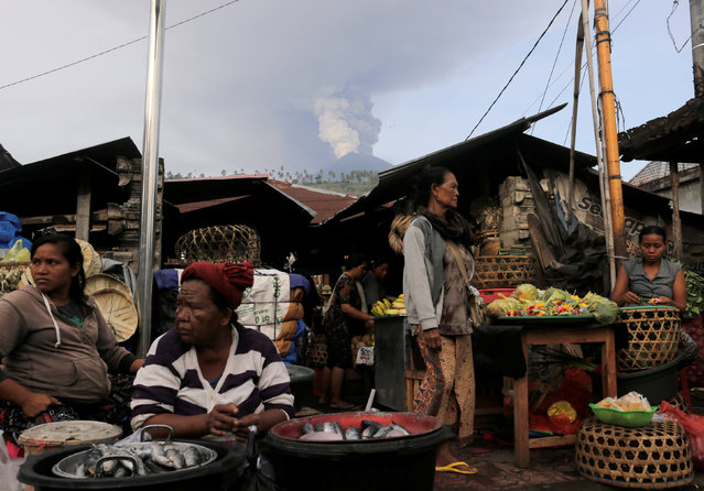 Balinese sell produce at a streetside market as Mount Agung volcano erupts at Culik village market in Karangasem, Bali, Indonesia on November 27, 2017. (Photo by Johannes P. Christo/Reuters)