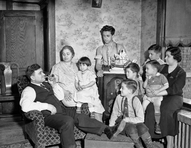 Frank Esposito finds comfort and happiness surrounded by his family after his duties as a worker in Illinois steel company's plant are completed for the day in south Chicago, March 3, 1937. Left to right: Esposito, his wife, Theresa holding Jean, 3; Jerry 15; John 12; Tom 10; Joe 7, and Della Fionda, his daughter, holding Joe, 2. (Photo by AP Photo)