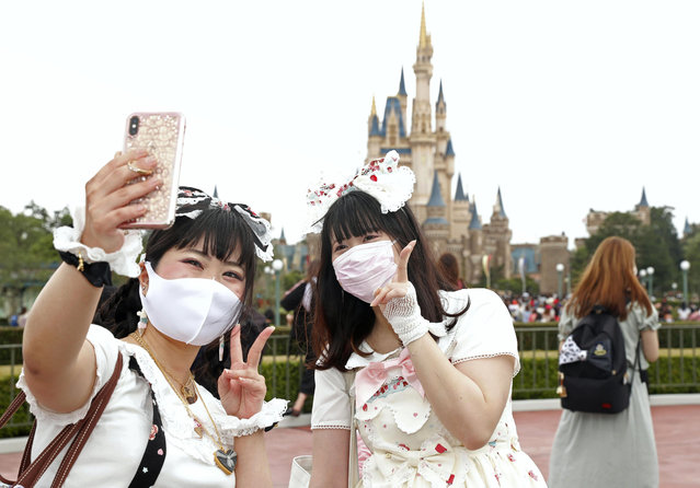 Visitors wearing face masks to protect against the spread of the new coronavirus take a selfie at Tokyo Disneyland in Urayasu, near Tokyo, Wednesday, July 1, 2020. Tokyo Disneyland reopens for the first time in four months after suspending operations due to coronavirus concerns. (Photo by Kyodo News via AP Photo)