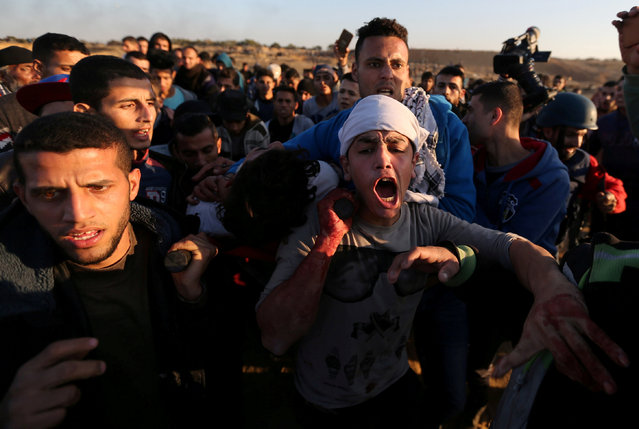 "A wounded Palestinian protester is evacuated during clashes with Israeli troops as Palestinians call for a ""day of rage"" in response to U.S. President Donald Trump's recognition of Jerusalem as Israel's capital, near the border with Israel in the central Gaza Strip December 8, 2017. (Photo by Ibraheem Abu Mustafa/Reuters)"